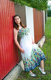 Girl in light dress against metal fence Stock Photo