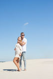A girl in a light dress leaned back against her man in the desert royalty free stock photography