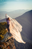 Girl with the light pink fabric playing with wind on mountains. Girl with the light pink fabric playing with wind Stock Photos