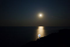Girl with light watching the full moon Stock Photography