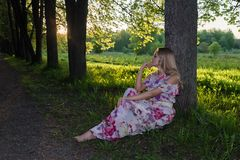 A girl with light wavy hair sits by a tree in the park Royalty Free Stock Images