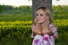 A girl with light wavy hair sits by a tree in the park Royalty Free Stock Photography
