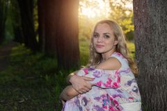 A girl with light wavy hair sits by a tree in the park Stock Images