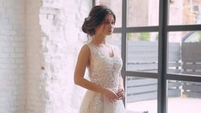Girl in a light white luxurious wedding dress poses, stands alone in a spacious room, the interior is in a Scandinavian