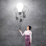 Girl with lightbulbs Stock Images