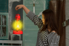 Girl with a lighted kerosene lamp at night in a vintage room Royalty Free Stock Photography