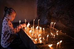 Girl lightening the candles royalty free stock image