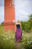 Girl at lighthouse. A young blond model posing near an old red lighthouse on the seaside Stock Images