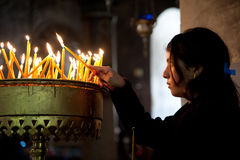 Girl lighting prayer candle. BETHLEHEM, OCCUPIED PALESTINIAN TERRITORIES - MARCH 18: A girl lights a prayer candle in the Church of the Nativity, traditional Royalty Free Stock Photography