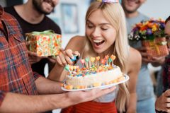 The girl lights the candles on the cake. Around her there are guests waiting for the celebration. Royalty Free Stock Photography