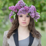 Girl with lilac flowers on head Stock Image