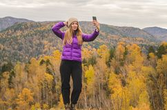 A girl in a lilac jacket makes a salfi on a mountain, a view of the mountains and an autumnal forest by a cloudy day. Free space for text royalty free stock images