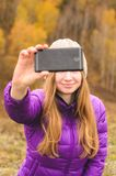 A girl in a lilac jacket makes a salfi on a mountain, a view of the mountains and an autumnal forest by a cloudy day. Free space for text Royalty Free Stock Image
