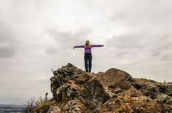 A girl in a lilac jacket stretching her arms on a mountain, a view of the mountains and an autumn forest by a cloudy day. Free space for text Royalty Free Stock Images