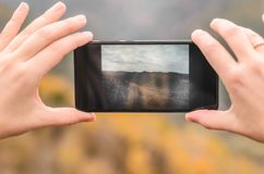 A girl in a lilac jacket takes pictures on a telephone in the mountains, an autumn forest with a cloudy day Stock Images