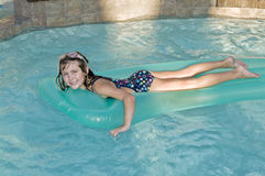 Girl on lilo. Happy young girl floating on lilo in swimming pool Stock Photo