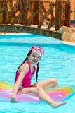 Girl on lilo in pool. Happy young girl playing on lilo in hotel swimming pool with bridge in background Stock Photo