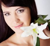 Girl with lily flower neare her face Stock Images
