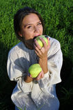 Girl in a linen shirt, eating apples Stock Photography