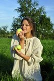 Girl in a linen shirt, holding apples Royalty Free Stock Photos