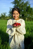 Girl in a linen shirt, holding a strawberry Royalty Free Stock Photos
