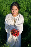 Girl in a linen shirt, holding a strawberry Stock Photo