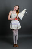 Girl in a linen sundress with sun umbrella. Smiling girl 12-13 years standing in studio with a sun umbrella on a dark background Stock Images