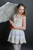Girl in a linen sundress with sun umbrella. Smiling girl 12-13 years standing in studio with a sun umbrella on a dark background Royalty Free Stock Photos