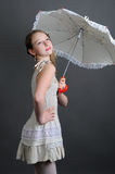 Girl in a linen sundress with sun umbrella. Girl 12-13 years standing in studio with a sun umbrella on a dark background Stock Photo