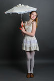 Girl in a linen sundress under parasol. Smiling girl 12-13 years standing in studio under an umbrella on a dark background Stock Photo