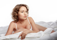 Girl in lingerie on the bed. Sexy brunette on white bed sheets. Stock Photos