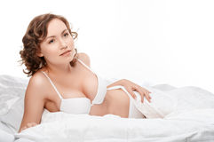 Girl in lingerie on the bed. Sexy brunette on white bed sheets. Royalty Free Stock Photos