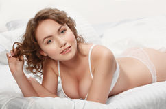 Girl in lingerie on the bed. Sexy brunette on white bed sheets. Royalty Free Stock Images