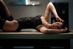 Girl in lingerie lying on the kitchen table Royalty Free Stock Images