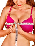 Girl in lingerie measures her breast measuring tape. Royalty Free Stock Image