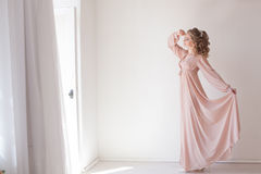 Girl in lingerie Pajamas pink. Girl bride in pink Pajamas posing in a white room Stock Photos