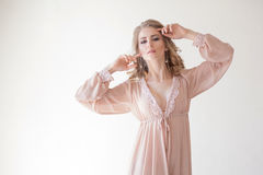 Girl in lingerie Pajamas pink. Girl bride in pink Pajamas posing in a white room Royalty Free Stock Images