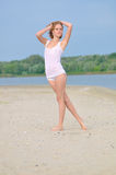 Girl in lingerie walking along the sandy beach Stock Image