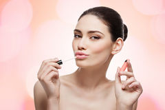Girl with lip gloss Stock Photos