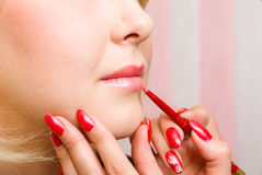 Girl of a lip paints visagiste with red  lipstick. Stock Images