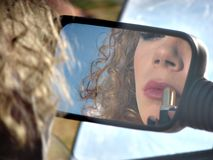 Girl with lipstick and mirror of car Royalty Free Stock Images