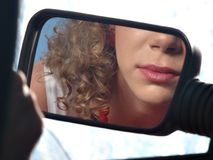 Girl with lipstick and mirror of car Stock Image