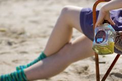 Girl with liquor on beach. A partial view of the legs of a woman, sitting on a chair on a beach holding a nearly empty bottle of hard liquor Stock Photography