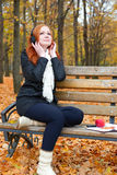 Girl listen music on audio player with headphones, sit on bench in city park, autumn season, yellow trees and fallen leaves Royalty Free Stock Image