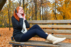 Girl listen music on audio player with headphones, sit on bench in city park, autumn season, yellow trees and fallen leaves Royalty Free Stock Photography