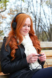 Girl listen music on audio player with headphones, sit on bench in city park, autumn season, yellow trees and fallen leaves Stock Photo