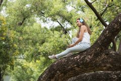 Girl listen music on big greenery tree. Asian Beautiful boho woman sit on big tree and listen to streaming music from smartphone by earbuds. Brunette bohemian Stock Image