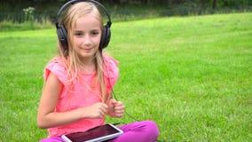 Girl listen music on tablet outdoors stock video
