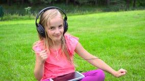 Girl listen music on tablet outdoors stock footage
