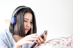 Girl listen using headphone and mobile phone. Stock Photography